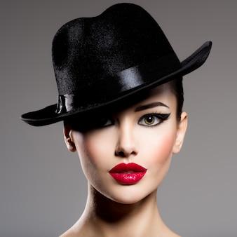 Nahaufnahmeporträt einer frau in einem schwarzen hut mit den roten lippen, die aufwerfen