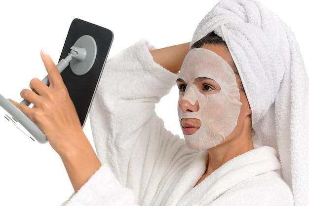 Nahaufnahmeporträt einer frau mit einer feuchtigkeitsspendenden stoffmaske auf ihrem gesicht, die in den spiegel schaut