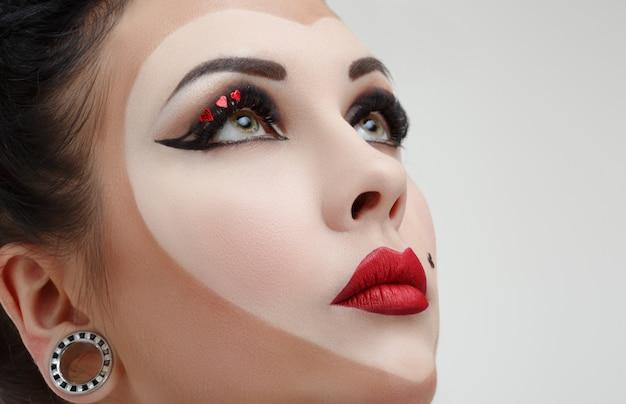 Nahaufnahmeporträt einer frau mit fantasie-make-up als spielkarte.