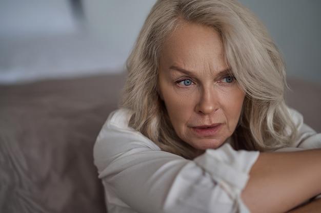 Nahaufnahmeporträt einer freudlosen blauäugigen blonden reifen frau mit einem in gedanken versunkenen blick in die ferne