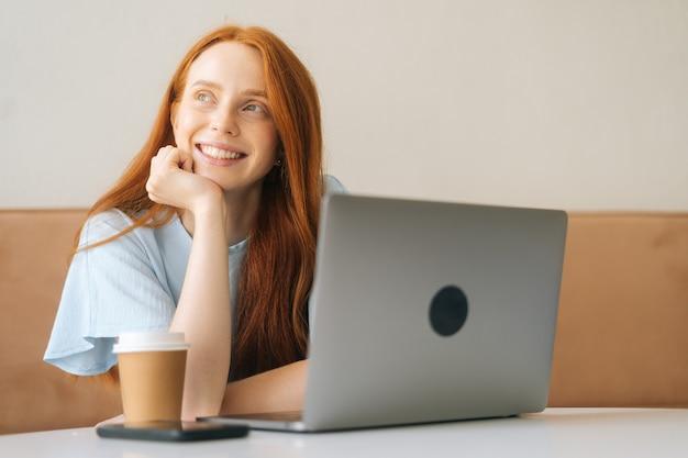 Nahaufnahmeporträt einer fröhlichen jungen schönen frau, die am schreibtisch mit laptop und tasse mit heißem kaffee im gemütlichen café sitzt und wegschaut. hübsche kaukasische dame der rothaarigen entfernt, die arbeitet oder studiert.