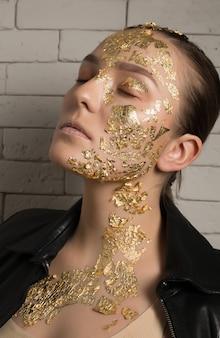 Nahaufnahmeporträt einer glamourösen brünetten frau mit goldfolie auf gesicht und hals, die mit geschlossenen augen posiert