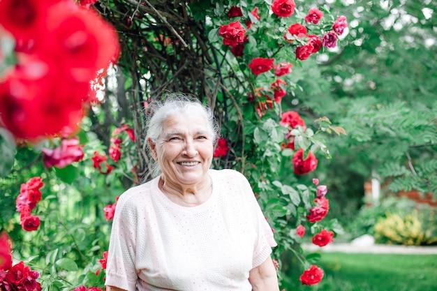 Nahaufnahmeporträt einer grauhaarigen älteren frau mit einem breiten lächeln und furnieren im garten