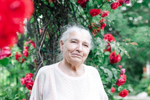 Nahaufnahmeporträt einer grauhaarigen faltigen alten dame in einem park nahe einer wilden rose