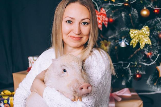 Nahaufnahmeporträt einer jungen frau mit einem minischwein in den dekorationen des neuen jahres