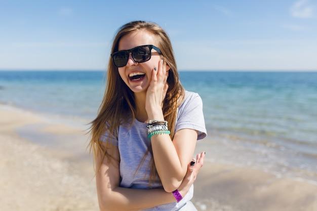 Nahaufnahmeporträt einer jungen hübschen frau mit langen haaren am strand