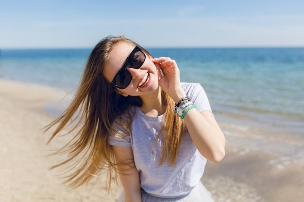 Nahaufnahmeporträt einer jungen hübschen frau mit langen haaren, die auf dem strand nahe meer gehen