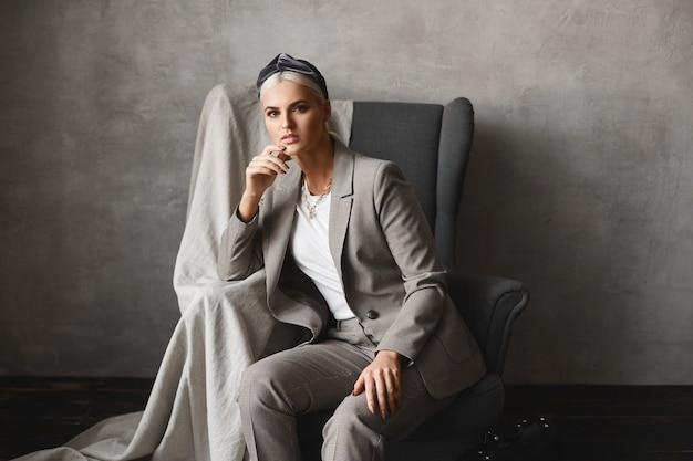 Nahaufnahmeporträt einer jungen kaukasischen frau mit blonden haaren, die nach vorne schaut, während sie im sessel sitzt wunderschöne junge geschäftsfrau in stilvollem anzug, die in einem leeren innenraum posiert