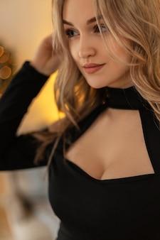 Nahaufnahmeporträt einer jungen schönen eleganten frau mit frisur in schwarzer stilvoller kleidung auf einem hintergrund goldener bokeh-lichter. modelmädchen auf einer party