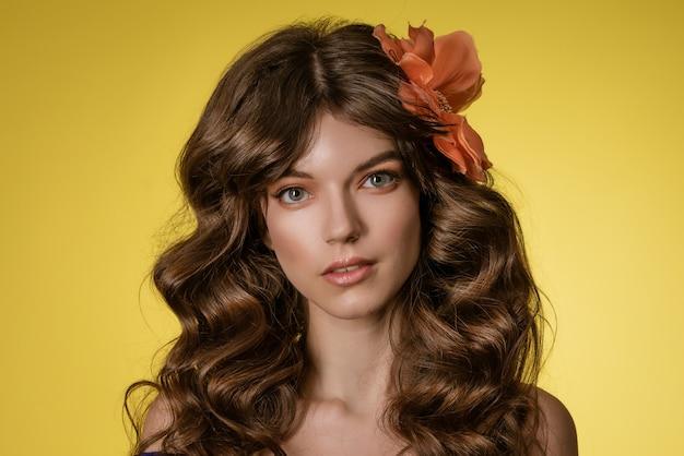 Nahaufnahmeporträt einer jungen schönen frau auf einem gelben hintergrund mit einer blume in ihren haaren