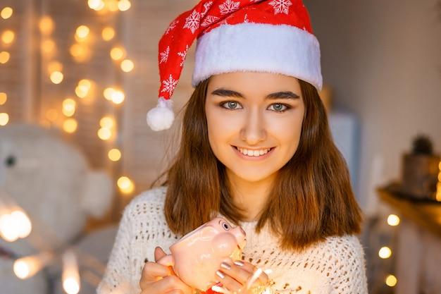 Nahaufnahmeporträt einer lachenden netten jungen frau mit einem sankt-hut auf ihrem kopf mit girlanden in ihren händen