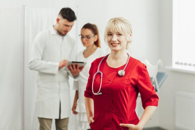 Nahaufnahmeporträt einer lächelnden ärztin in einer roten uniform mit einem stethoskop.