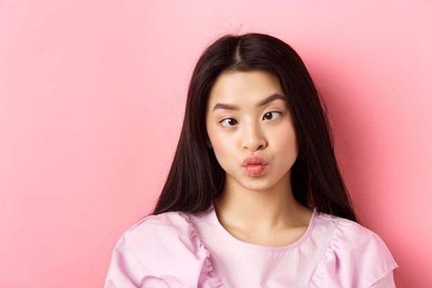 Nahaufnahmeporträt einer lustigen asiatischen frau, die augen zusammenkneift und dumme gesichter macht, die gegen rosa ba...