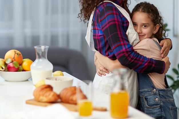 Nahaufnahmeporträt einer mutter umarmen ihre süße tochter in der küche in der nähe des tisches, frühstücken zusammen.
