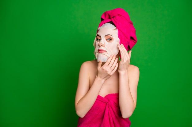 Nahaufnahmeporträt einer netten hübschen dame mit turban mit gesichtsmaske, die sich einzeln auf hellgrünem farbhintergrund vorbereitet