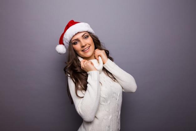 Nahaufnahmeporträt einer niedlichen weihnachtsfrau mit einer roten weihnachtsmannmütze, weißem kleid, lächelnd, glücklich, auf ferienzeit wartend. positive emotion auf isolierter grauer wand.