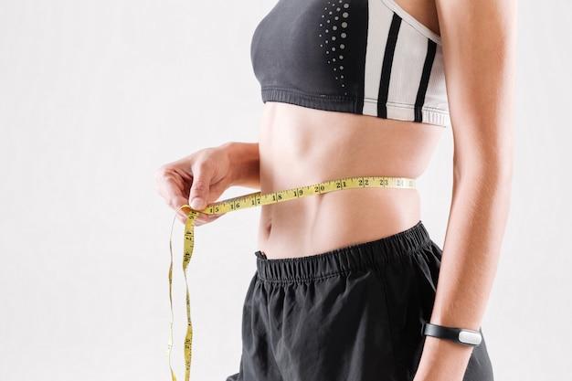 Nahaufnahmeporträt einer schlanken sportlerin, die ihre taille misst