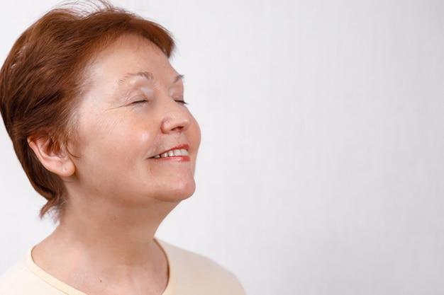 Nahaufnahmeporträt einer schönen älteren frau, die zur seite auf weiß in einem hellen t-shirt schaut. isoliert