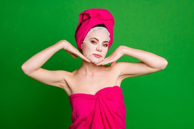 Nahaufnahmeporträt einer schönen attraktiven gesunden dame mit turban-kollagen-gesichts-baumwollmaske, die isoliert auf hellgrünem farbhintergrund berührt