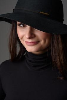 Nahaufnahmeporträt einer schönen frau, die einen schwarzen hut trägt.