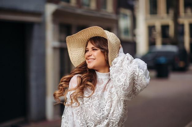 Nahaufnahmeporträt einer schönen frau in einem vintagen sommerhut. eine schöne frau in einem boho-strohhut und kleid.