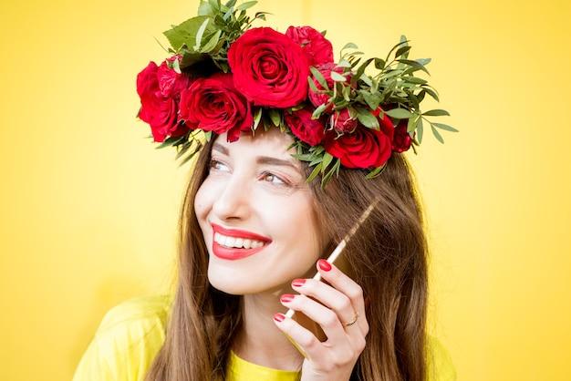 Nahaufnahmeporträt einer schönen frau mit kranz aus roten rosen, die mit telefon auf gelbem hintergrund spricht