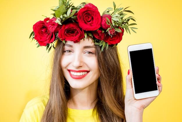 Nahaufnahmeporträt einer schönen frau mit kranz aus roten rosen, die telefon mit leerem bildschirm auf gelbem hintergrund hält