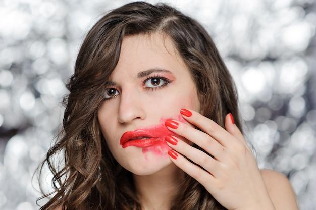 Nahaufnahmeporträt einer schönen frau mit leuchtend rotem lippenstift. die frau rieb sich den lippenstift vom gesicht.