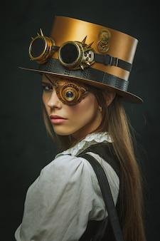 Nahaufnahmeporträt einer schönen frau steampunk, hut und augenmuschel.
