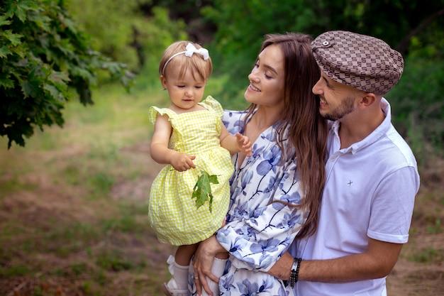 Nahaufnahmeporträt einer schönen jungen familie, die am warmen sommertag ein kleines, stilvolles baby im grünen park trägt