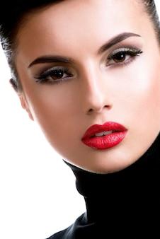 Nahaufnahmeporträt einer schönen jungen frau mit mode-make-up, das lokalisiert auf weiß aufwirft.