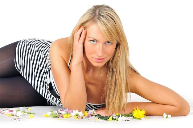 Nahaufnahmeporträt einer schönen jungen geheimnisvollen sexy blonden frau, die im studio auf einem weiß mit blumen aufwirft