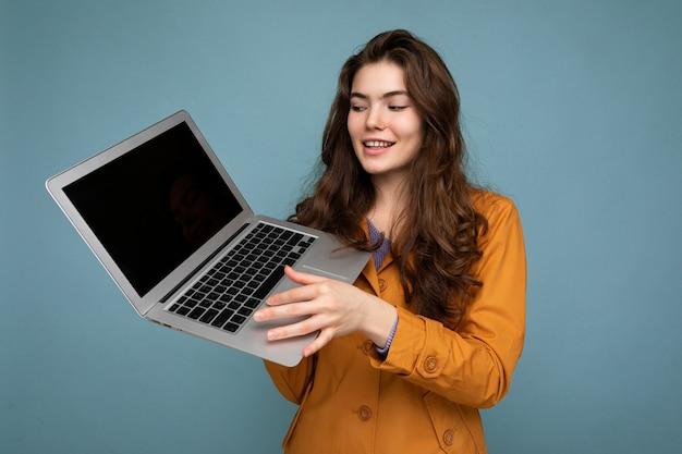 Nahaufnahmeporträt einer schönen lächelnden, glücklichen jungen frau, die einen computer-laptop hält und das netbook anschaut