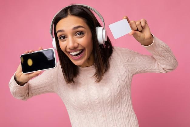Nahaufnahmeporträt einer schönen überglücklichen jungen brünetten frau, die einen rosa lässigen pullover trägt, isoliert über einer rosa hintergrundwand, die weiße drahtlose bluetooth-kopfhörer trägt und musik und show hört