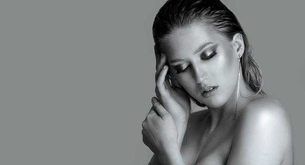Nahaufnahmeporträt einer sinnlichen jungen frau mit dem nassen haar und den bloßen schultern über einem grauen hintergrund. platz für text