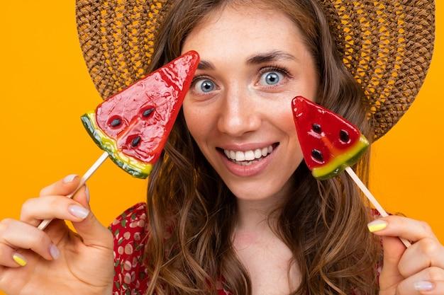Nahaufnahmeporträt einer stilvollen frau mit sommerbonbons in ihren händen