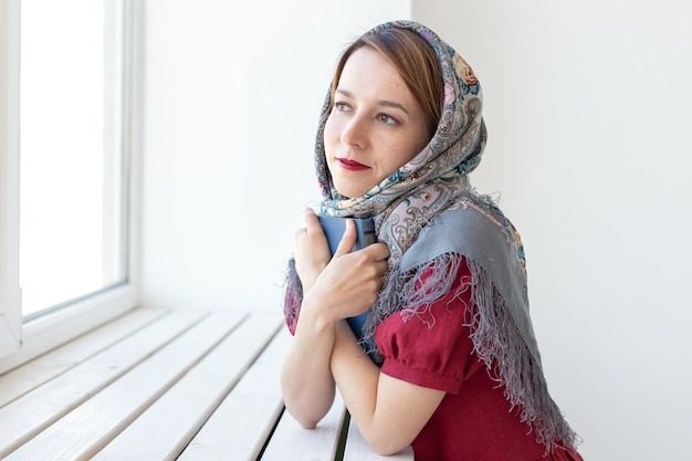 Nahaufnahmeporträt einer süßen jungen verträumten frau mit einem buch in der hand, die aus dem fenster schaut und an etwas denkt. konzeptliebhaber von klassikern und literatur.