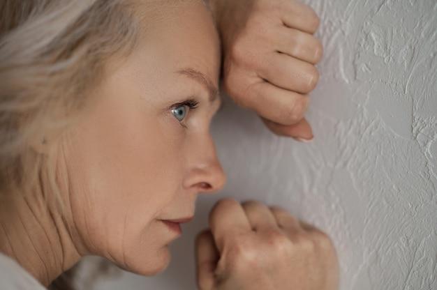 Nahaufnahmeporträt einer traurigen nachdenklichen blauäugigen blonden frau, die ihr gesicht an die weiße wand drückt