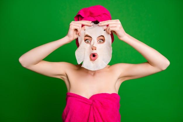 Nahaufnahmeporträt einer verwunderten funky dame mit turban mit gesichtsmaske wie gruseligen geisterschmollenlippen einzeln auf hellgrünem hintergrund