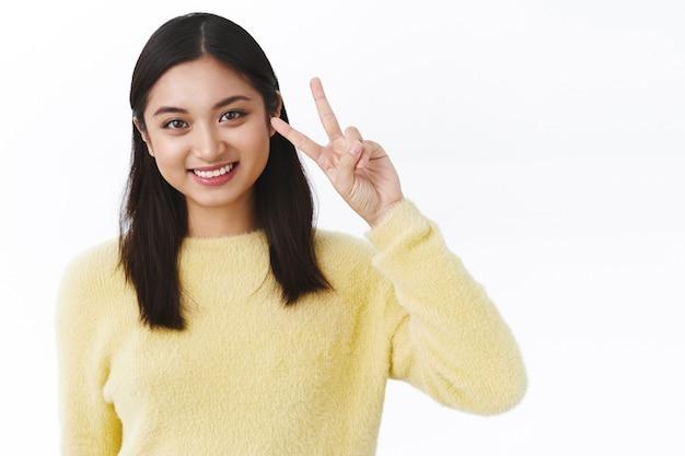 Nahaufnahmeporträt einer zarten kawaii asiatischen frau in gelbem pullover mit friedensgeste, goodwill-zeichen und lächeln, kamera suchen, hautpflegeprodukt, mode- oder schönheitskonzept fördern