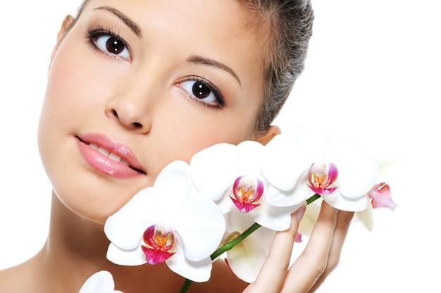 Nahaufnahmeporträt eines asiatischen schönheitsmädchens mit blume nahe ihrem gesicht - hautpflegebehandlung