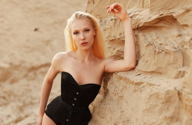 Nahaufnahmeporträt eines blonden mädchens im schwarzen bodysuit, der in der nähe von caree-sand in der wüste posiert. Premium Fotos