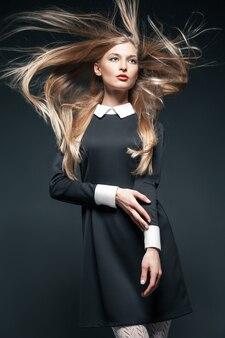Nahaufnahmeporträt eines blonden models, das mit im wind flatternden haaren posiert