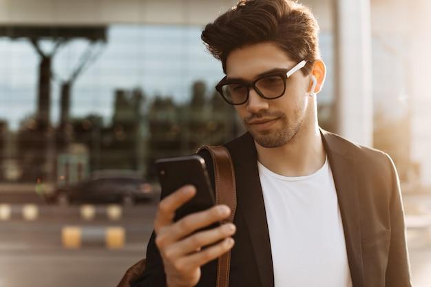 Nahaufnahmeporträt eines brünetten jungen mannes mit brille, weißem t-shirt und schwarzer jacke mit telefon und messaging