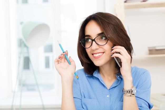 Nahaufnahmeporträt eines brünetten mädchens, das im büro sitzt. sie trägt ein blaues hemd und hält einen bleistift in der hand. sie spricht am telefon.