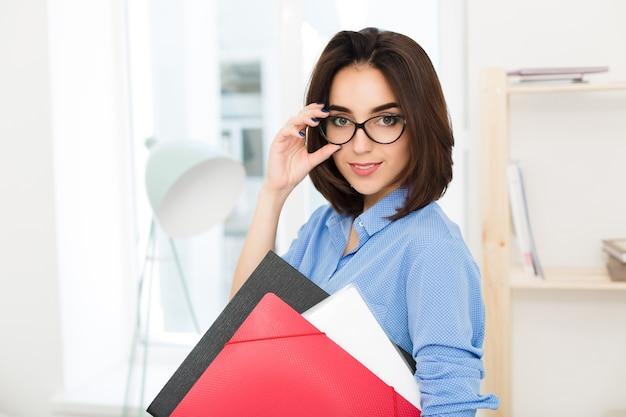Nahaufnahmeporträt eines brünetten mädchens, das im büro steht. sie hält ordner in einer hand und brillen im gesicht in einer anderen.