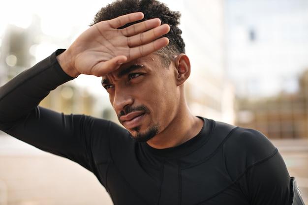 Nahaufnahmeporträt eines dunkelhäutigen brünetten bärtigen mannes im schwarzen langärmeligen t-shirt berührt sein gesicht und sieht direkt nach draußen