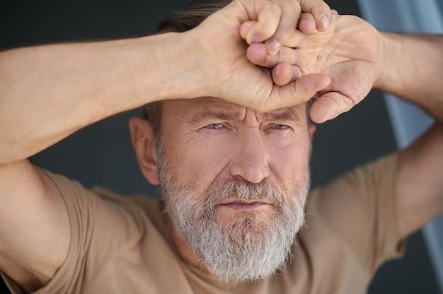 Nahaufnahmeporträt eines ernsten nachdenklichen grauhaarigen kaukasischen kerls, der gegen das glas gelehnt ist und nach vorne starrt