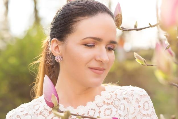 Nahaufnahmeporträt eines erstaunlichen brünetten modells mit nacktem make-up, das in der nähe der blühenden magnolienblumen posiert
