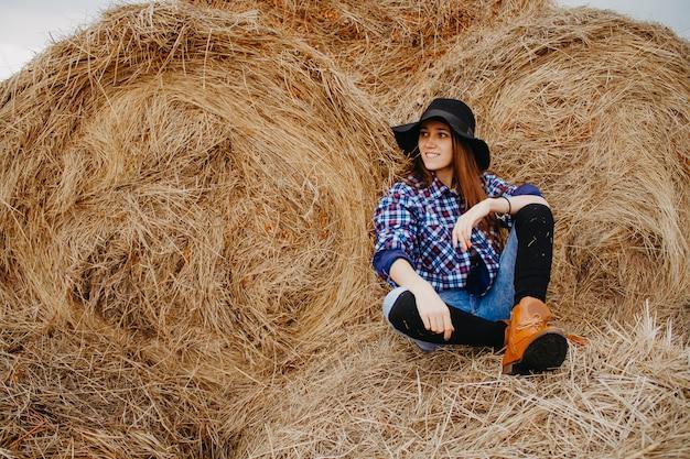 Nahaufnahmeporträt eines frauenlandwirts, eine frau, die auf einem heuschober in einem schwarzen hut sitzt, schaut weg